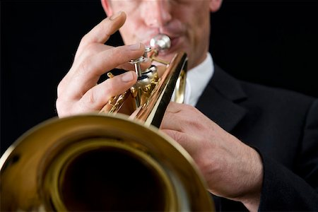 finger holding a key - Man playing a trumpet Stock Photo - Premium Royalty-Free, Code: 653-01662457