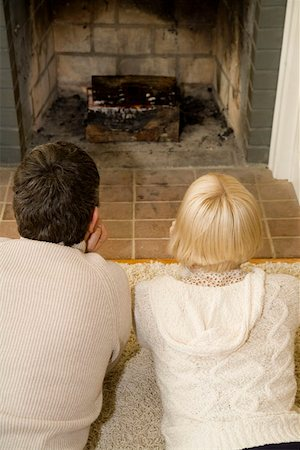 sweater and fireplace - Young couple lying down in front of an open fire together Stock Photo - Premium Royalty-Free, Code: 653-01662717
