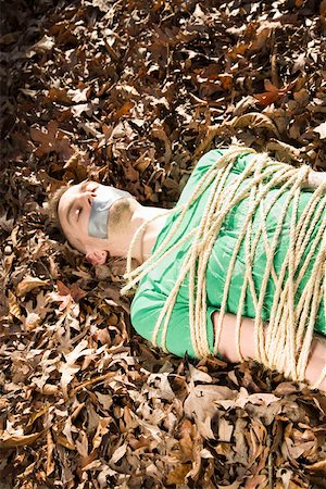 restrained - Man lying on the ground, bound in rope and with adhesive tape covering his mouth Stock Photo - Premium Royalty-Free, Code: 653-01662809