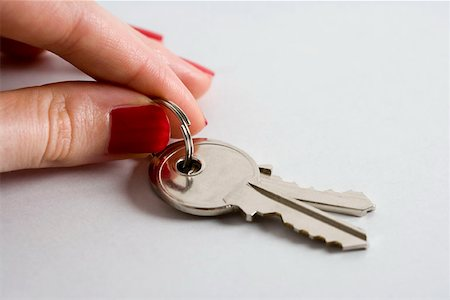 finger holding a key - A woman holding keys Stock Photo - Premium Royalty-Free, Code: 653-01697575
