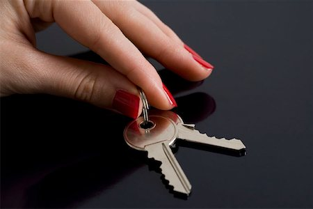 finger holding a key - A woman picking up some keys Stock Photo - Premium Royalty-Free, Code: 653-01697581