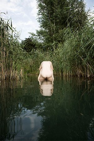 A naked woman resting on the back of a naked man standing in a pond Stock Photo - Premium Royalty-Free, Code: 653-01698161