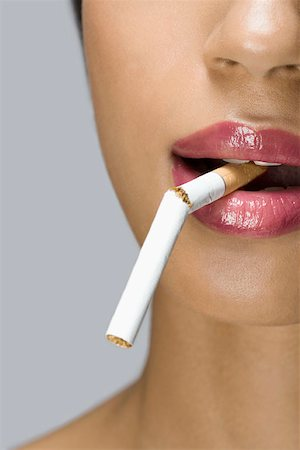 A woman with a broken cigarette in her mouth Stock Photo - Premium Royalty-Free, Code: 653-01698357