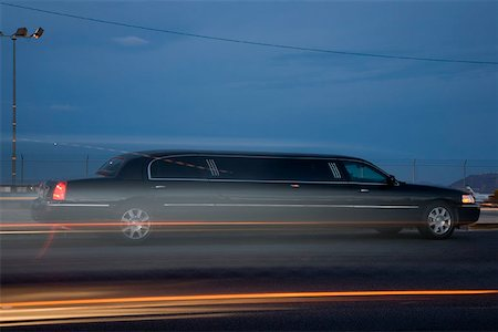 A limousine driving along the road Stock Photo - Premium Royalty-Free, Code: 653-01698625