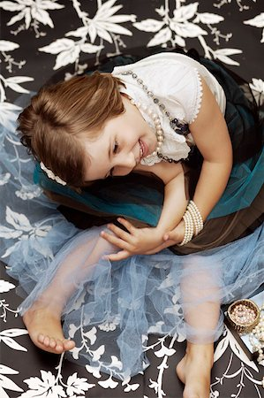Portrait of a young girl playing dress up with costume jewelry Stock Photo - Premium Royalty-Free, Code: 653-02001506