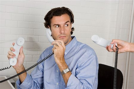 A businessman with three telephone receivers Stock Photo - Premium Royalty-Free, Code: 653-02001837
