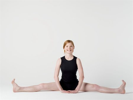 A young woman beginning the 'Spread Leg Forward Fold' yoga pose Stock Photo - Premium Royalty-Free, Code: 653-02260276