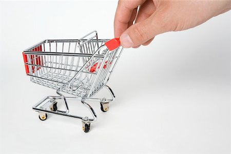 empty shopping cart - A miniature empty shopping cart being pushed by human fingers Stock Photo - Premium Royalty-Free, Code: 653-02260361