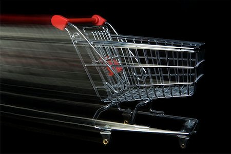 empty shopping cart - A miniature empty shopping cart moving,blurred motion Stock Photo - Premium Royalty-Free, Code: 653-02260372