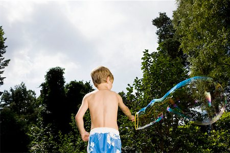 A boy making a bubble with a bubble wand Stock Photo - Premium Royalty-Free, Code: 653-02261016