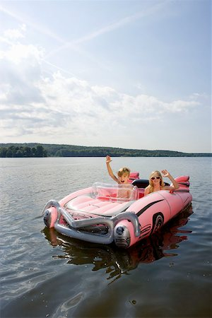 Two children in an inflatable raft on a lake Stock Photo - Premium Royalty-Free, Code: 653-02261025