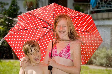Two children standing under an umbrella and getting hit by spraying water Stock Photo - Premium Royalty-Free, Code: 653-02261043