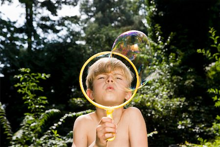 A boy blowing a bubble with a bubble wand Stock Photo - Premium Royalty-Free, Code: 653-02261051