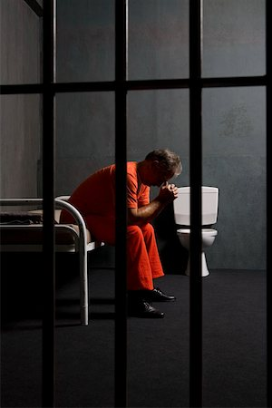 A prisoner sitting on a bed in a prison cell Stock Photo - Premium Royalty-Free, Code: 653-02261091
