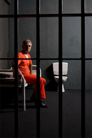 Prisoner sitting on a bed in a prison cell Stock Photo - Premium Royalty-Free, Code: 653-02261093