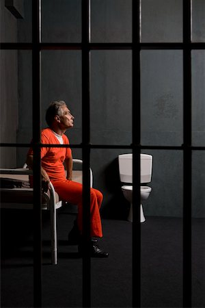 A prisoner sitting in his prison cell Stock Photo - Premium Royalty-Free, Code: 653-02261113