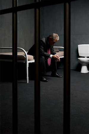 A businessman sitting on a bed in a prison cell Stock Photo - Premium Royalty-Free, Code: 653-02261124