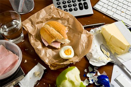 An office desk cluttered with food Stock Photo - Premium Royalty-Free, Code: 653-02634146