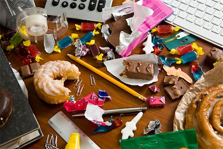 An office desk cluttered with candy and sweets Stock Photo - Premium Royalty-Free, Code: 653-02634148