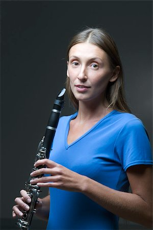 A young woman holding a clarinet Stock Photo - Premium Royalty-Free, Code: 653-02634492