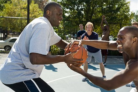 Two basketball players fighting over a basketball Stock Photo - Premium Royalty-Free, Code: 653-02634732