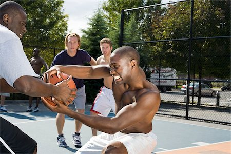 Two basketball players fighting over a basketball Stock Photo - Premium Royalty-Free, Code: 653-02634744