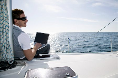 Rear view of a man using a laptop on a yacht Stock Photo - Premium Royalty-Free, Code: 653-02635034