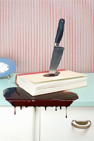 dripping blood - Knife stabbing a book on a dresser Stock Photo - Premium Royalty-Free, Code: 653-02635213