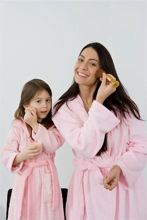 A mother and daughter in pink bathrobes applying make up Stock Photo - Premium Royalty-Free, Code: 653-02834149