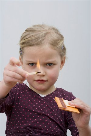 A young girl playing with matches Stock Photo - Premium Royalty-Free, Code: 653-02834212