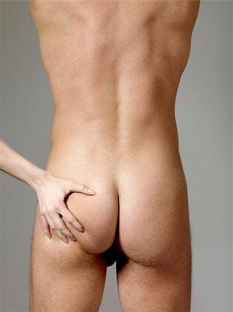 Detail of a woman grabbing a naked man's bottom Stock Photo - Premium Royalty-Free, Code: 653-02834830