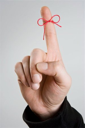 string - A bow tied around a man's index finger Stock Photo - Premium Royalty-Free, Code: 653-02834919