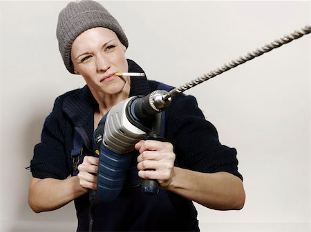 A woman holding a large drill Stock Photo - Premium Royalty-Free, Code: 653-02835082