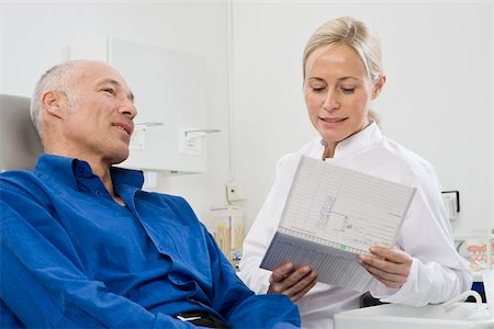 A dentist talking to a patient sitting in a dentist's chair Stock Photo - Premium Royalty-Free, Code: 653-02835175