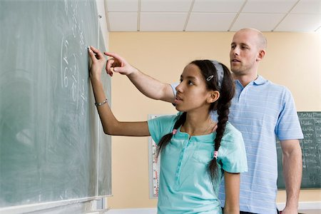 A girl writing on a blackboard with a teacher standing beside Stock Photo - Premium Royalty-Free, Code: 653-02835180