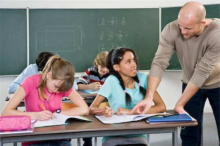 A teacher working with students in a classroom Stock Photo - Premium Royalty-Free, Code: 653-02835228