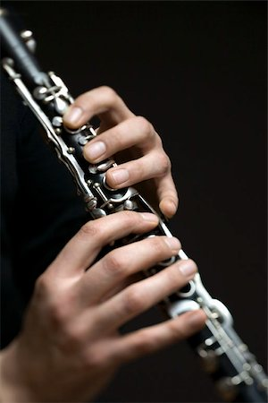 Human hands playing a clarinet Stock Photo - Premium Royalty-Free, Code: 653-02835395