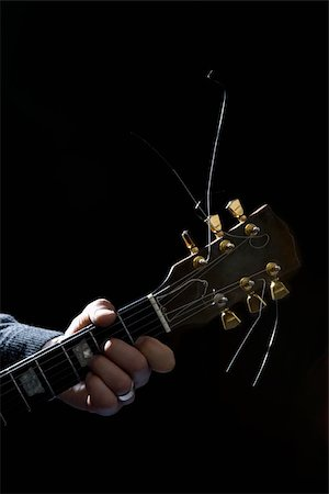 finger holding a key - Detail of a man playing an electric guitar Stock Photo - Premium Royalty-Free, Code: 653-02835785