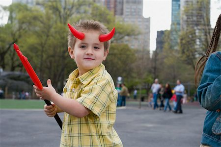A young boy wearing devils horns and holding a pitchfork, Central Park, New York City Stock Photo - Premium Royalty-Free, Code: 653-02835933