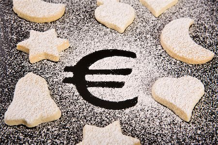 The Euro symbol in powdered sugar surrounded by various shaped cookies Stock Photo - Premium Royalty-Free, Code: 653-03078978