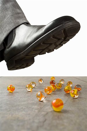 dangerous accident - A foot above scattered marbles Stock Photo - Premium Royalty-Free, Code: 653-03079695