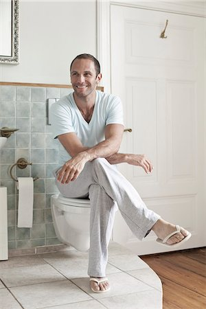 A man sitting on the toilet in the bathroom Stock Photo - Premium Royalty-Free, Code: 653-03334028