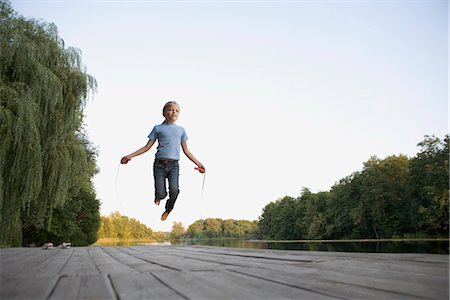 A girl skipping on a wooden jetty Stock Photo - Premium Royalty-Free, Code: 653-03334185