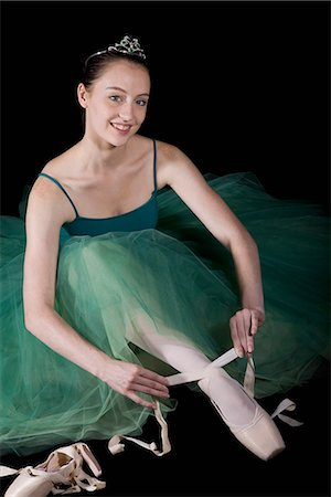 A ballet dancer wearing a costume tying her pointe shoe Stock Photo - Premium Royalty-Free, Code: 653-03334246