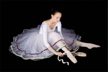 A ballet dancer tying her pointe shoe Stock Photo - Premium Royalty-Free, Code: 653-03334249
