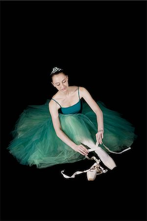A ballet dancer wearing a costume tying her pointe shoe Stock Photo - Premium Royalty-Free, Code: 653-03334262
