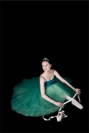 A ballet dancer wearing a costume tying her pointe shoe Stock Photo - Premium Royalty-Free, Code: 653-03334273