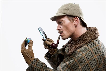 A man dressed up as Sherlock Holmes looking at a tiny globe through a magnifying glass Stock Photo - Premium Royalty-Free, Code: 653-03334456