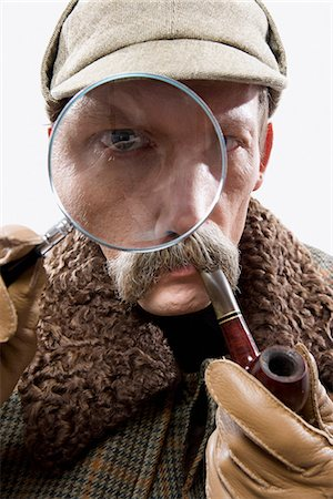 A man dressed up as Sherlock Holmes with a magnifying glass distorting his eye Stock Photo - Premium Royalty-Free, Code: 653-03334458