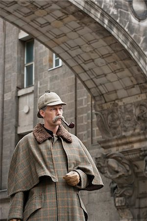 A man dressed up as Sherlock Holmes standing under a building arch looking away Stock Photo - Premium Royalty-Free, Code: 653-03334461